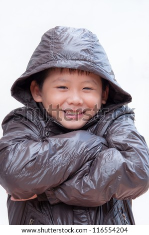 Smiling little asian boy in winter coat.