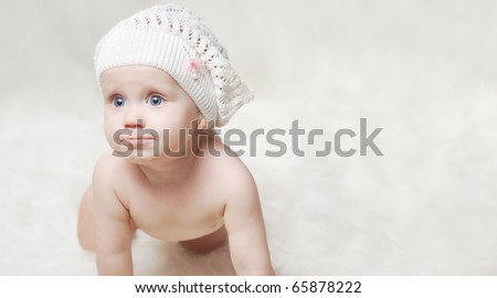 Smiling little baby on a soft blanket with hat
