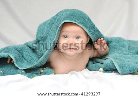 Smiling Little Baby with beautiful blue eyes wrapped in a bath towel