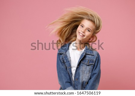 Smiling little blonde kid girl 12-13 years old in denim jacket isolated on pastel pink background children portrait. Childhood lifestyle concept. Mock up copy space. Having fun with fluttering hair Stock photo ©