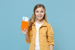 Smiling little blonde kid girl 12-13 years old in yellow jacket isolated on blue background. Passenger traveling abroad to travel on weekends getaway. Air flight journey concept. Hold passport ticket