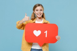 Smiling little blonde kid girl 12-13 years old in yellow jacket isolated on blue wall background. Childhood lifestyle concept. Hold huge like sign from social network heart form, showing thumb up