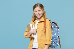 Smiling little blonde kid girl 12-13 years old wearing yellow jacket with backpack hold books isolated on pastel blue background studio portrait. Childhood lifestyle concept. Education in school.