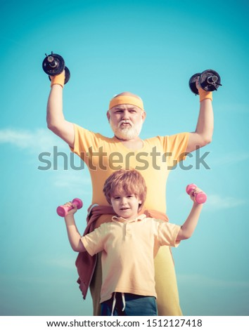 Smiling little boy and happy handsome old man exercising with dumbbells. Lifting dumbbells. Children repeat exercise after granddad. Doing sports is free