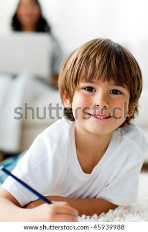Smiling little boy drawing lying on the floor in the living-room - stock photo