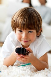 Smiling little boy holding a remote lying on the floor in the living-room