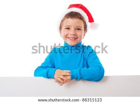Smiling little boy in Santa's hat with empty banner, isolated on white