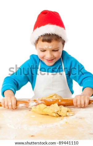 Smiling little boy kneading the dough for Christmas cooking, isolated on white