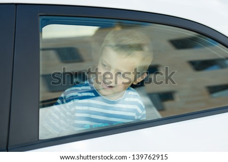 Smiling little boy looking out in the window car