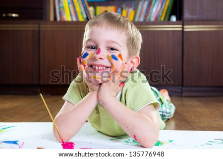 Smiling little boy lying on floor and painting