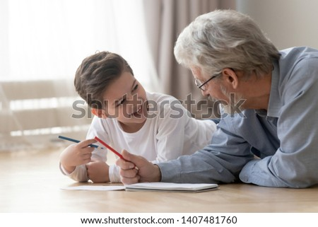Smiling little boy lying on floor having fun enjoy painting in album together with loving grandfather, grandparent spend time teaching drawing picture entertaining at home with excited small grandson