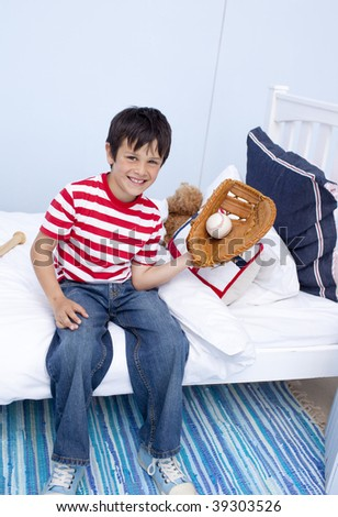 Smiling little boy playing baseball in his bedroom