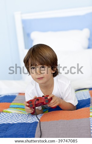 Smiling little boy playing videogames in his bedroom