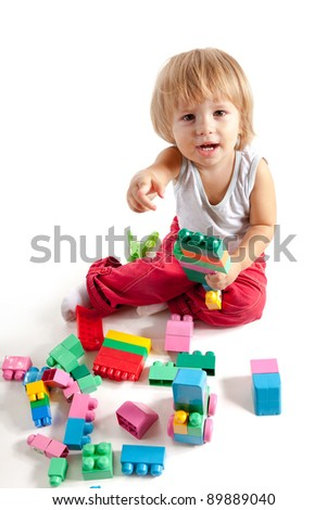 Smiling little boy playing with blocks, isolated on white background