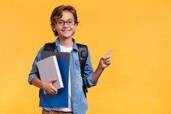 Smiling little boy pointing at copy space in casual clothes with books for studing at school isolated over yellow background