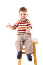 Smiling little boy sitting on stool, isolated on white