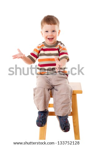 Smiling little boy sitting on stool, isolated on white