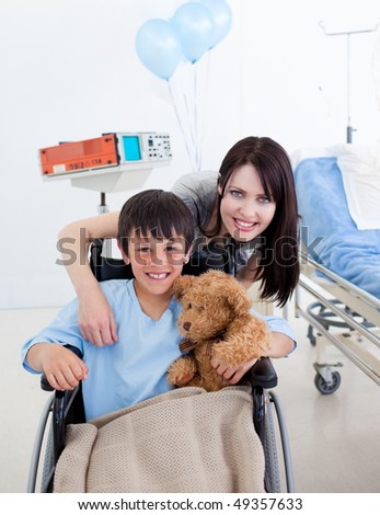 Smiling little boy sitting on wheelchair and his mother at the hospital