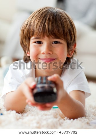 Smiling little boy watching TV lying on the floor in the living-room