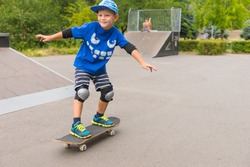 Smiling little boy whizzing along on a skateboard at a skate park as he enjoys the freedom of his summer vacation