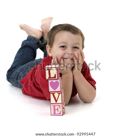 """smiling little boy with a stack of blocks that spell """"love"""""""