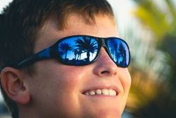 Smiling little boy with blue sunglasses at sunny day outdoors. Palm trees reflection on eyeglasses of happy kid enjoying summer holidays. Childhood joy, ultraviolet light, eyes protection concepts