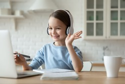 Smiling little Caucasian girl in headphones have video call distant class with teacher using laptop, happy small child wave greeting with tutor, study online on computer, homeschooling concept