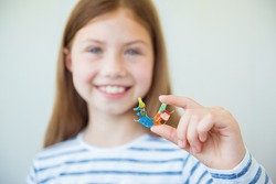 Smiling little child girl holds metal bright and colorful plate for align the teeth and bite. Orthodontist treats teeth