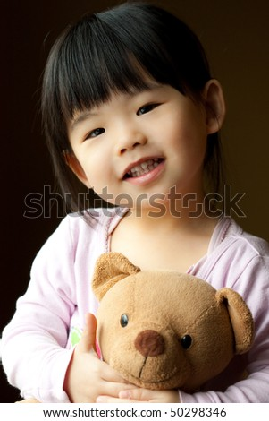 Smiling little child holding a teddy bear in her hand