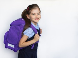 smiling little cute schoolgirl in uniform with school bag, backpack, isolated on white background, 1 september
