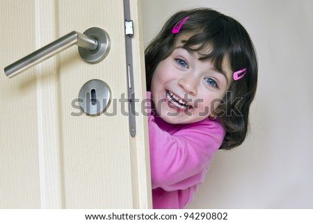 Smiling little enjoys girl is hiding behind a door
