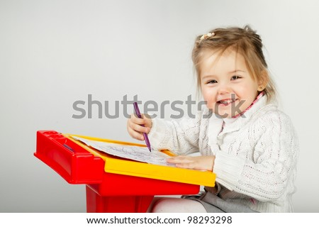 Smiling little girl at the table draw