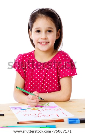 Smiling little girl at the table draw with crayons for mum, isolated on white