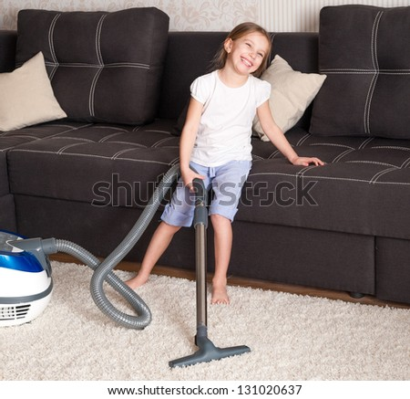 smiling little girl cleaning the room - using vacuum cleane