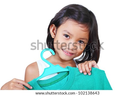 Smiling little girl holding a shirt in hanger.