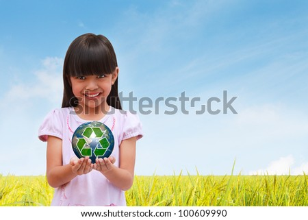 Smiling little girl holding earth with recycle symbol, Elements of this image furnished by NASA