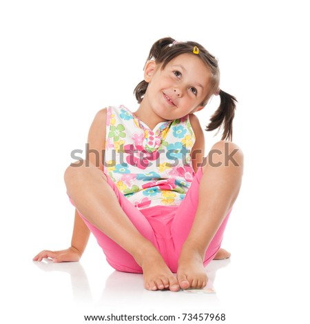 Smiling little girl imaging and sitting on floor isolated on white background