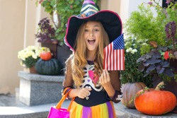 Smiling little girl in Halloween witch costume with USA flag near the house. Happy child.