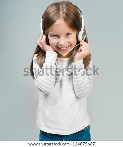 Smiling little girl in headset looks into camera