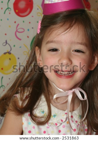 smiling little girl in party hat at her birthday party