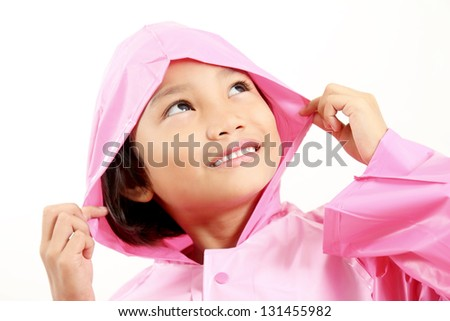 Smiling little girl in pink raincoat looking upward.Close up.