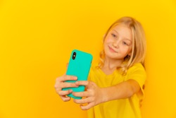 Smiling little girl kid showing blue screen of new popular mobile phone on light yellow background.