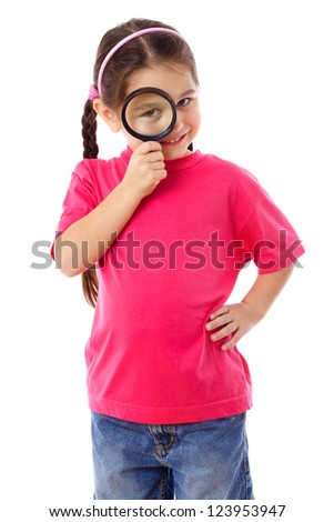 Smiling little girl looking through a magnifying glass, isolated on white