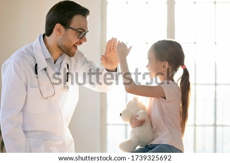 Smiling little girl patient give high five have fun at consultation with excited male doctor or pediatrician, happy small child client greeting with man GP in hospital or clinic, healthcare concept