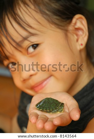 Smiling little girl showing her lovely little tortoise