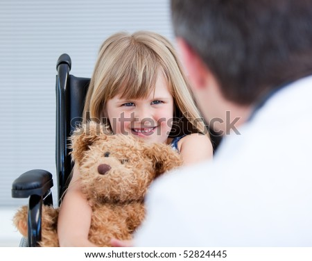 Smiling little girl sitting on the wheelchair with her teddy bear at the hospital
