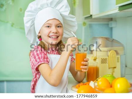 Smiling little girl tastes freshly prepared apple-carrot juice