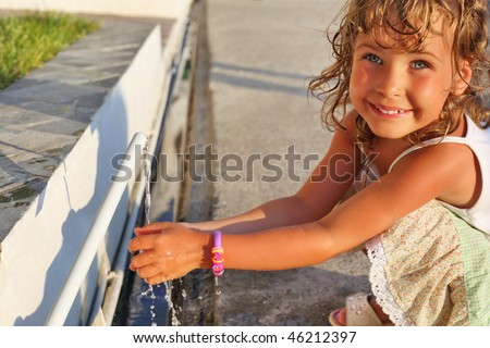 Smiling little girl washes hands water from pipe in street