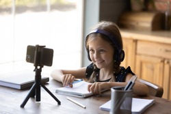 Smiling little girl wearing headphones studying online at home, looking at phone screen, watching webinar, engaged in video conference, using smartphone on tripod, writing notes, homeschooling