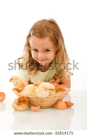 Smiling little girl with a basket full of young chickens - isolated